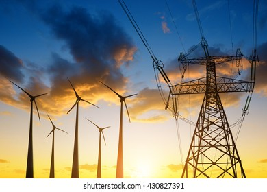 High voltage tower and wind turbines against the sunset