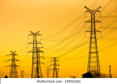 High voltage towers against the sunset background.
