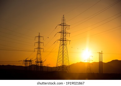 high voltage towers in the desert with sunset