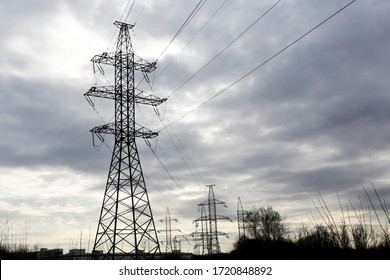 High voltage towers with electrical wires on dark cloudy sky background. Electricity transmission lines, electric power station
