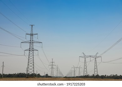 High voltage towers with electricity transmission power lines in field on sunny day
