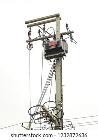 High voltage transformer with low voltage and low voltage fuse on the concrete pole for power supply to small users. White sky background.