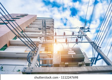 High voltage transformer pole are connecting the electrical system to the condominium.The concept of electrical systems for building.Electricity transmission station.Energy cable.