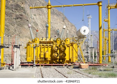 High voltage transformer at power plant. Mountain and blue sky