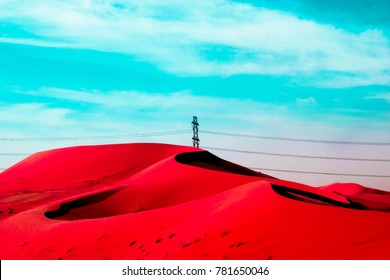 high voltage transmission electricity supply line on a red desert dunes with blue sky in the background