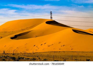 high voltage transmission electricity supply line on a desert dunes with blue sky in the background
