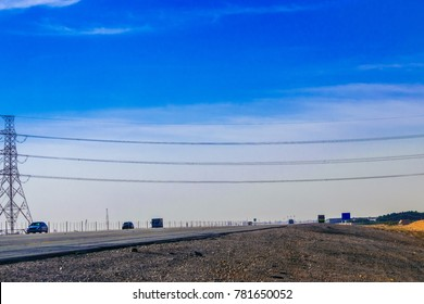 high voltage transmission electricity supply line on top of a busy highway with blue sky in the background