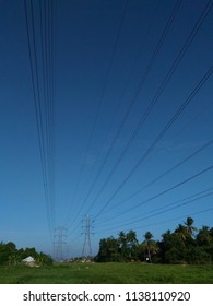 High voltage transmission lines with blue sky background.