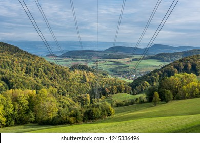 High voltage transmission lines running through green forest over green lawn with blue sky and mountains in the background