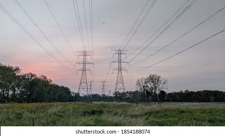 High voltage transmission lines with sun setting behind them at Sterling State Park in Monroe Michigan