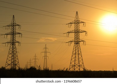High voltage transmission lines at sunset. Energy and electrification.