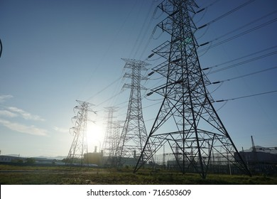 High voltage transmission tower or power tower (electricity pylon) and electrical distribution substation during sunrise