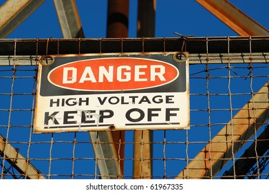 High voltage warning sign on a rusted tower