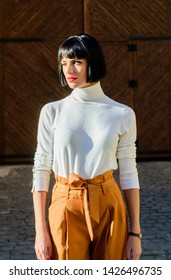High waisted. Femininity and emphasize feminine figure. Girl makeup face wear loose high waisted pants. High waisted trousers keep returning to catwalk. Woman attractive brunette fashionable outfit.