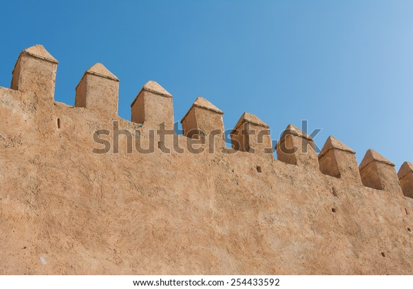 High wall made with clay under blue sky