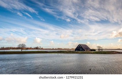 High water level in the Noordwaard polder of the Biesbosch, Noord-Brabant, the Netherlands. The old barn (built in 1900) is protected against the water by a ring dike. Its is a stormy day in winter.
