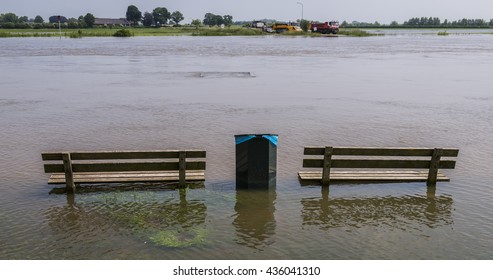 High water on the IJssel with the ferry of Dieren and two benches in the water in The Netherlands.