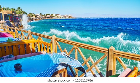 The high wind and strong stormy waves in Dahab resort, the coastal cafes at the shore of Aqaba Gulf open the view on the mountains of Saudi Arabia, seen behind the sea, Sinai, Egypt.