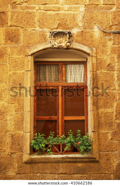 High window with flowers on the windowsill in the city of Valletta - the capital city of Malta.