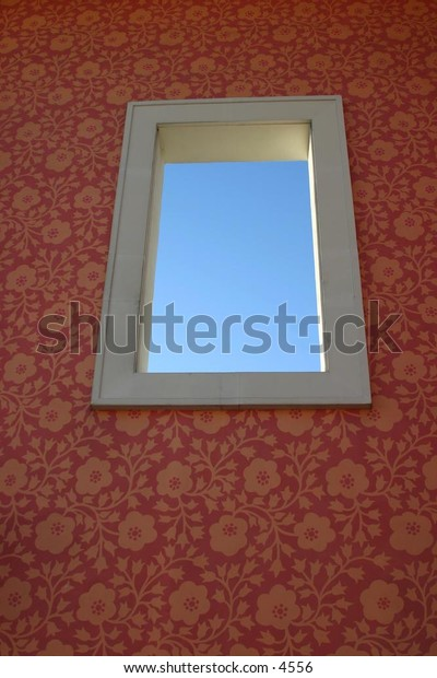 high window on wallpapered wall looking out a sky
