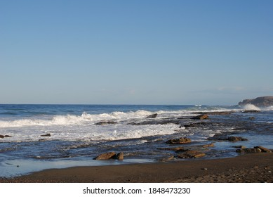 High winds drive waves to shore and against the rocks where spray and foam