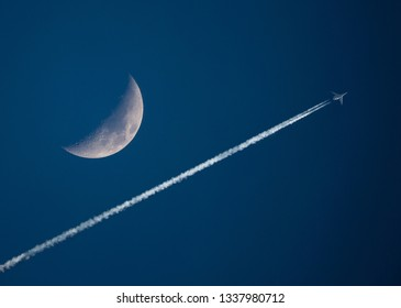 A high-altitude jet with contrails passes by a crescent moon in a dark blue sky at sunset.