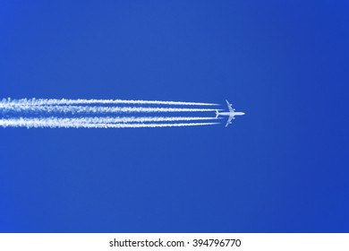 High-altitude jumbo jet airplane in a blue sky