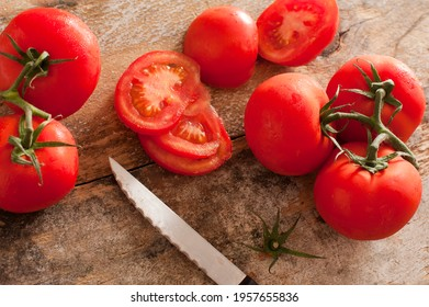 High-angle close-up view of fresh and juicy tomatoes as a nutritious ingredient next to a knife on a rustic wooden table