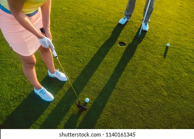 High-angle cropped view of a professional woman player, holding the putter golf club ready to hit the ball into the hole at the end of a difficult game with her partner or instructor