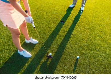 High-angle cropped view of a professional woman player holding the putter golf club, ready to hit the ball into the hole at the end of a difficult game with her partner or instructor
