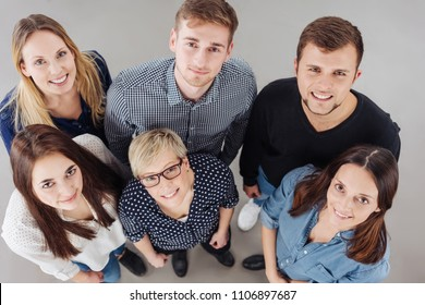 High-angle group portrait of six young and confident people smiling while looking at camera as a reliable professional team