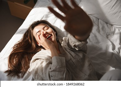 High-angle of happy young woman lying in bed and stretching hand up, laughing and having fun with someone.
