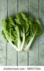 high-angle shot of a bunch of raw chard leaves on a rustic pale green wooden table