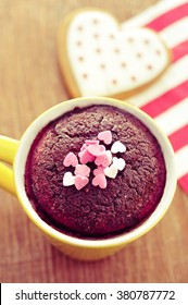 high-angle shot of a chocolate mug cake topped with heart-shaped confetti sprinkles and a heart-shaped cookie on a wooden table, with a filter effect