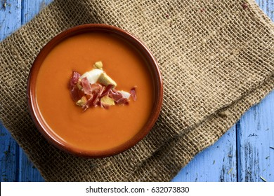 high-angle shot of an earthenware bowl with spanish salmorejo cordobes or porra antequerana, a cold tomato soup topped with serrano ham and croutons, on a blue rustic table