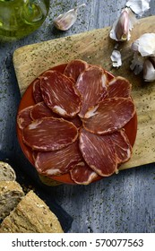 high-angle shot of a plate with some slices of spanish lomo embuchado, cured pork tenderloin, some slices of bread, a glass cruet with olive oil and some garlics, on a rustic gray wooden table