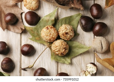 high-angle shot of a roasted sweet potato, some chestnuts and some panellets, as a typical snack eaten in All Saints Day in Catalonia, Spain, called castanada, and some autumn leaves on a wooden table