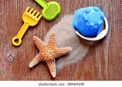 high-angle shot of a rustic wooden surface with a starfish on a pile, and some beach toys such as a shovel, a rake and a pail