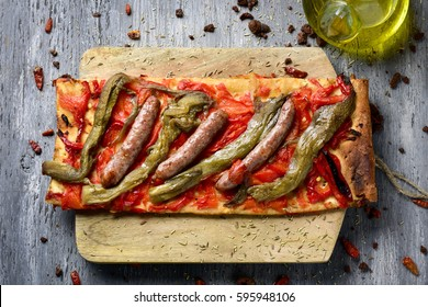 high-angle shot of a slice of coca de recapte, a typical catalan savory cake similar to pizza, made with grilled eggplant and red pepper, and pork sausage, on a rustic wooden table