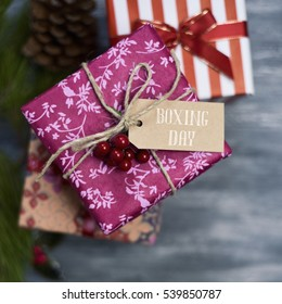 high-angle shot of some cozy gifts wrapped in different nice papers and tied with ribbons and strings of different colors, with a paper tag tied to one of them with the text boxing day