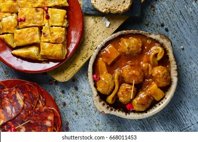 high-angle shot of some plates with different spanish cold meats and tapas, such as spanish omelette, meatballs with cuttlefish or sliced chorizo on a gray rustic wooden table
