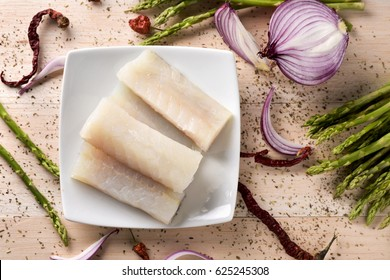 high-angle shot of some slices of raw codfish in a white ceramic plate, some wild asparagus, some chilli peppers and half purple onion, on a rustic wooden table