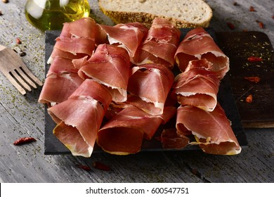 high-angle shot of some slices of spanish serrano ham on a wooden chopping board, and some slices of bread and a glass cruet with olive oil on a rustic wooden table