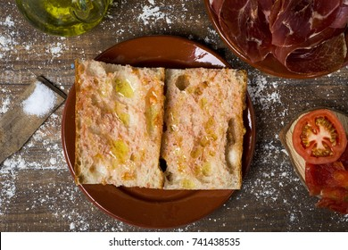 high-angle shot of typical catalan pa amb tomaquet, bread with tomato, placed on a plate, on a rustic wooden table next to a plate with some slices of serrano ham, tomato and a cruet with olive oil