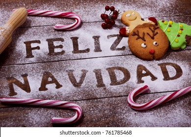 high-angle shot of a wooden table sprinkled with icing sugar or flour where you can read the text feliz navidad, merry christmas in spanish, a rolling pin, some candy canes and some christmas cookies