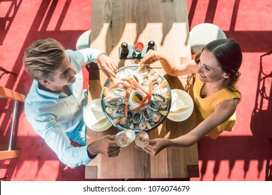 High-angle view of a happy young couple toasting with champagne during romantic dinner with fresh seafood at a trendy restaurant