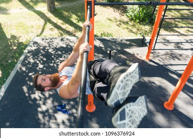High-angle view of a strong and determined young man doing hanging oblique leg raises for abdominal muscles during street workout