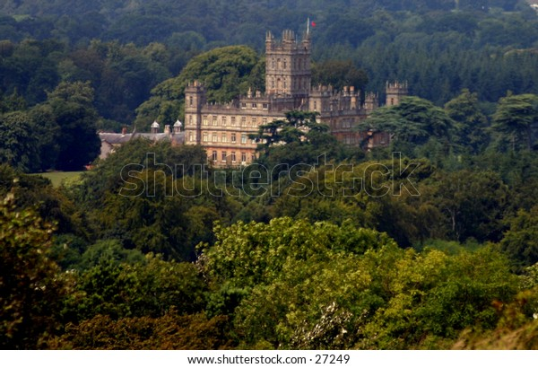 Highclere castle England viewed from teh top of a nearby hill situated in a forrest of trees