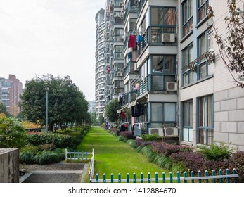 High-density residential apartment buildings and courtyard with green grass and trees. City of Ningbo, Zhejiang, China.