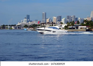 High-end cabin cruiser speeding on the Florida Intra-Coastal Waterway off Miami Beach with Miami tall building skyline in the background.